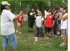 Crow Canyon educator and students, spear-throwing activity.