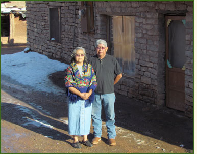 A Pueblo couple standing in front of their home.