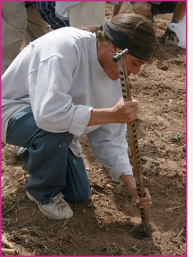 A Pueblo farmer using a metal digging stick to plant seed.