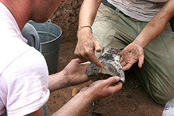 Archaeologists excavate a large pottery sherd